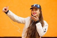 Το νέο κορίτσι hipster ομορφιάς στην ΚΑΠ και τα γυαλιά ηλίου κάνουν selfie από το smartphone και ακούνε μουσική από τα ακουστικά  Στοκ φωτογραφίες με δικαίωμα ελεύθερης χρήσης