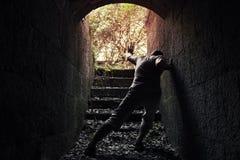 Το νέο κουρασμένο άτομο αφήνει τη σκοτεινή σήραγγα πετρών Στοκ φωτογραφίες με δικαίωμα ελεύθερης χρήσης