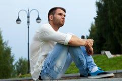 Το νέο κουρασμένο άτομο κάθεται στα σύνορα στο θερινό πάρκο στοκ φωτογραφία με δικαίωμα ελεύθερης χρήσης