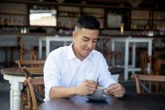 Το νέο λατινικό άτομο πίνει τον καφέ στον καφέ οδών στοκ εικόνες
