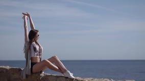Το νέο λεπτό κορίτσι κάθεται στο φράκτη πετρών και αυξάνεται τα χέρια της επάνω φιλμ μικρού μήκους