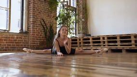 Το νέο λεπτό όμορφο κορίτσι κάνει κάποιο σπάγγο για να τεντώσει τα πόδια της Χαριτωμένο αθλητικό κορίτσι που κάνει τις διασπάσεις απόθεμα βίντεο