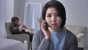 Το νέο λυπημένο ασιατικό κορίτσι σχηματίζει αγωνιωδώς έναν αριθμό, καλεί από το smartphone, πορτρέτο, εξετάζει τη κάμερα, πιωμένο απόθεμα βίντεο