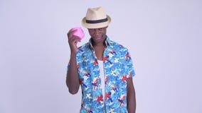 Το νέο λυπημένο αφρικανικό άτομο τουριστών που τινάζει τη piggy τράπεζα και που δίνει φυλλομετρεί κάτω απόθεμα βίντεο