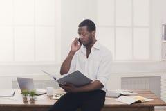 Το νέο μαύρο επιχειρηματία που διαβάζεται τα έγγραφα και τη συζήτηση σε κινητό στο νεαρό δικυκλιστή Στοκ Φωτογραφίες