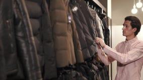 Το νέο μελαχροινό άτομο ελέγχει την ποιότητα των χειμερινών σακακιών που κρεμούν σε ένα κατάστημα φιλμ μικρού μήκους