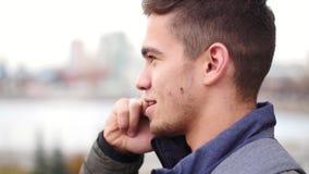 Το νέο μοντέρνο άτομο μιλά στο τηλέφωνο και τα χαμόγελα στην πόλη σε αργή κίνηση απόθεμα βίντεο