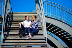 Το νέο μοντέρνο ζεύγος κάθεται στα σκαλοπάτια στην ηλιόλουστη ημέρα στοκ εικόνες