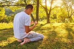 Το νέο μουσουλμανικό άτομο προσεύχεται στη φύση στο χρόνο ηλιοβασιλέματος Στοκ Εικόνες