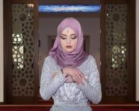Το νέο μουσουλμανικό κορίτσι προσεύχεται στο μουσουλμανικό τέμενος Στοκ Εικόνες