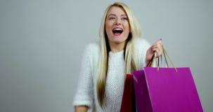Το νέο ξανθό θηλυκό πρότυπο κάνει τις εκφράσεις του ενθουσιασμού με τις ζωηρόχρωμες συσκευασίες αγορών στα χέρια της απόθεμα βίντεο
