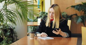 Το νέο ξανθό κορίτσι εργάζεται με ένα smartphone sittig στον πίνακα στον καφέ Απασχολείται και πίνει στον καφέ απόθεμα βίντεο