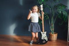 Το νέο ξανθό κορίτσι με τις ουρές στην άσπρα μπλούζα, τη φούστα και τα σανδάλια με την ηλεκτρική κιθάρα παρουσιάζει στο σπίτι αντ στοκ εικόνες