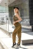 Το νέο ξανθό κορίτσι που ντύνεται στο μοντέρνο παντελόνι και τη τοπ χακί μαύρης ΚΑΠ χρώματος και στο κεφάλι θέτει στην οδό στοκ εικόνες με δικαίωμα ελεύθερης χρήσης