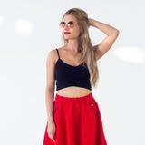 Το νέο ξανθό πρότυπο που παρουσιάζει το νέο μοντέρνο καλοκαίρι κοιτάζει, φορώντας τα γυαλιά ηλίου κύκλων, την κόκκινη φούστα και  Στοκ Φωτογραφίες
