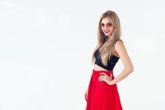 Το νέο ξανθό πρότυπο που παρουσιάζει το νέο μοντέρνο καλοκαίρι κοιτάζει, φορώντας τα γυαλιά ηλίου κύκλων, την κόκκινη φούστα και  Στοκ εικόνα με δικαίωμα ελεύθερης χρήσης