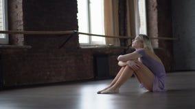 Το νέο ξανθό ballerine ανέτρεψε και κάθεται στο πάτωμα φιλμ μικρού μήκους