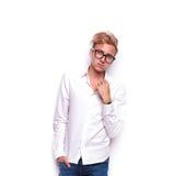 Το νέο ξανθό hipster που φορά τα γυαλιά που θέτουν με παραδίδει την τσέπη στοκ εικόνες