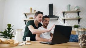 Το νέο ομοφυλοφιλικό ζεύγος στην κουζίνα αγκαλιάζει και έχει το πρόγευμα στον πίνακα γευμάτων χρησιμοποιώντας Διαδίκτυο στο lap-t απόθεμα βίντεο
