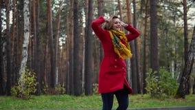 Το νέο περπάτημα γυναικών στο δασικό κορίτσι φθινοπώρου απολαμβάνει μια θερμή ημέρα φθινοπώρου Το κορίτσι στο κόκκινα παλτό και τ φιλμ μικρού μήκους