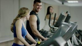 Το νέο περπάτημα γυναικών treadmill και μιλά στο νεαρό άνδρα φιλμ μικρού μήκους