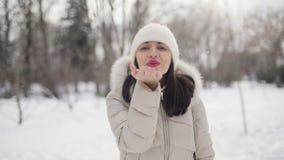 Το νέο πορτρέτο γυναικών τρίχας Brunette με τα ρόδινα χείλια στο μπεζ κάτω παλτό και το καπέλο στέλνει ένα φιλί αέρα στο χιονώδες απόθεμα βίντεο