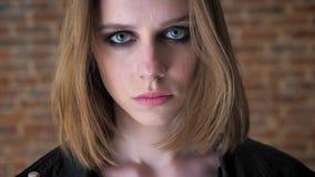 Το νέο προκλητικό εξαγριωμένο κορίτσι με τα καπνώδη μάτια προσέχει στη κάμερα, υπόβαθρο τούβλου, θολωμένο υπόβαθρο φιλμ μικρού μήκους