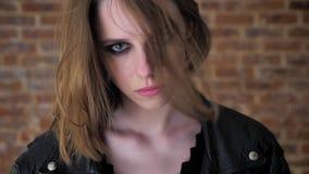 Το νέο προκλητικό κορίτσι με τα καπνώδη μάτια προσέχει στη κάμερα, τρίχα στο πρόσωπο, ιδιαίτερες προσοχές, υπόβαθρο τούβλου, που  φιλμ μικρού μήκους