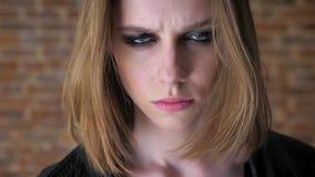 Το νέο προκλητικό κορίτσι με τα καπνώδη μάτια προσέχει στη κάμερα, ηρεμώντας κάτω, υπόβαθρο τούβλου, θολωμένο υπόβαθρο απόθεμα βίντεο