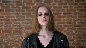 Το νέο προκλητικό κορίτσι με τα καπνώδη μάτια προσέχει στη κάμερα, θλίψη, υπόβαθρο τούβλου φιλμ μικρού μήκους