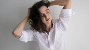 Το νέο προκλητικό κορίτσι στο άσπρο πουκάμισο στέκεται στον άσπρο τοίχο και απολαμβάνει απόθεμα βίντεο