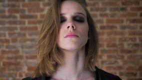 Το νέο προκλητικό σοβαρό κορίτσι με τα καπνώδη μάτια προσέχει στη κάμερα, κλείνει τα μάτια της, υπόβαθρο τούβλου φιλμ μικρού μήκους