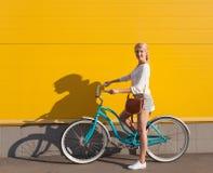 Το νέο προκλητικό ξανθό κορίτσι στέκεται κοντά στο εκλεκτής ποιότητας πράσινο ποδήλατο με την καφετιά εκλεκτής ποιότητας τσάντα Στοκ Φωτογραφία