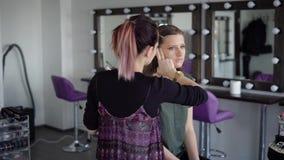 Το νέο πρότυπο ήρθε αρχικά στον επαγγελματικό καλλιτέχνη makeup σε ένα νέο σαλόνι μόδας Ένα κορίτσι με τη βαμμένη τρίχα ισχύει πρ φιλμ μικρού μήκους