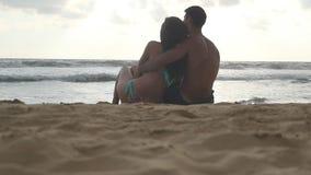Το νέο ρομαντικό ζεύγος απολαμβάνει την όμορφη συνεδρίαση άποψης στην παραλία και αγκαλιάζει στο βράδυ Μια γυναίκα και ένας άνδρα απόθεμα βίντεο