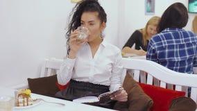 Το νέο σγουρό brunette διαβάζει το βιβλίο στον καφέ απόθεμα βίντεο