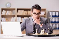 Το νέο σκάκι παιχνιδιού επιχειρηματιών στο γραφείο Στοκ Φωτογραφία