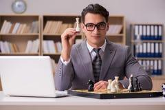 Το νέο σκάκι παιχνιδιού επιχειρηματιών στο γραφείο Στοκ Εικόνες