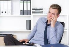 Το νέο στοχαστικό άτομο κάθεται στο γραφείο στο γραφείο Στοκ Εικόνες