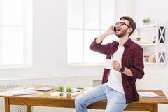 Το νέο συγκεντρωμένο επιχειρηματία που διαβάζεται τα έγγραφα στο σύγχρονο άσπρο γραφείο Στοκ φωτογραφία με δικαίωμα ελεύθερης χρήσης