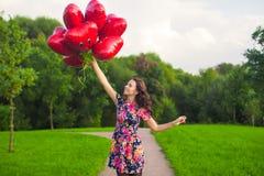 Το νέο συμπαθητικό κορίτσι στο όμορφο φόρεμα με τα κόκκινα μπαλόνια έχει τη διασκέδαση υπαίθρια Στοκ εικόνες με δικαίωμα ελεύθερης χρήσης