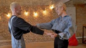 Το νέο σύγχρονο ζεύγος των hipsters χορεύει, φίλημα, έννοια αγάπης, υπόβαθρο τούβλου απόθεμα βίντεο