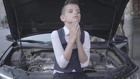 Το νέο τονισμένο καλά-ντυμένο αγόρι που στέκεται μπροστά από το σπασμένο αυτοκίνητο με μια ανοικτή κουκούλα Το αγόρι δοκιμάζει φιλμ μικρού μήκους