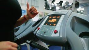 Το νέο τρέξιμο γυναικών, καρδιο κατάρτιση, treadmill, κορίτσι συμμετέχει σε έναν προσομοιωτή στη γυμναστική, αθλητισμός για το λε φιλμ μικρού μήκους