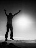Το νέο τρελλό άτομο πηδά στην αιχμή βουνών το ευτυχές πηδώντας άτομο χεριών έννοιας αύξησε τη νίκη σκιαγραφιών Στοκ φωτογραφίες με δικαίωμα ελεύθερης χρήσης