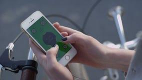 Το νέο χέρι γυναικών κινηματογραφήσεων σε πρώτο πλάνο στο ποδήλατο παίρνει Smartphone απόθεμα βίντεο