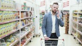Το νέο χαμογελώντας άτομο στο άσπρο πουκάμισο μιλά στο smartphone και περπατά μεταξύ των ραφιών με τα αγαθά στην υπεραγορά, stead φιλμ μικρού μήκους