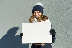 Το νέο χαμογελώντας κορίτσι το χειμώνα κρατά ένα καθαρό άσπρο φύλλο του εγγράφου στοκ εικόνες