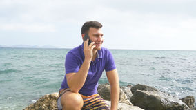 Το νέο χαμογελώντας άτομο μιλά στο κινητό τηλέφωνο στην παραλία στη θάλασσα Όμορφη ευτυχής συνεδρίαση τύπων στην πέτρα κοντά στον Στοκ Εικόνα
