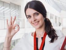 Το νέο χαμογελώντας κορίτσι που γίνεται την επιτυχή εργασία παρουσιάζει στη χειρονομία μεγάλο αντίχειρα Όμορφη χαμογελώντας επιχε Στοκ φωτογραφία με δικαίωμα ελεύθερης χρήσης